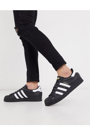 adidas Superstar trainers in black