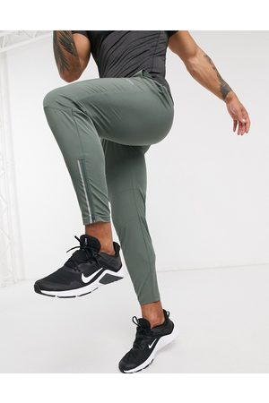 ASOS Hombre Pantalones - Woven skinny tapered running joggers with reflective zip detail in khaki