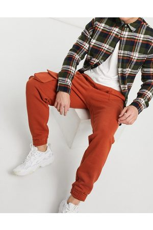 ASOS DESIGN Tapered joggers with multi utility pockets & tab cuffs in burnt red