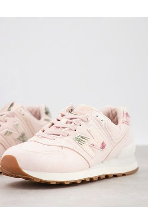 New Balance 574 trainers in pink with leaf print details
