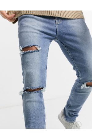 ASOS Enhanced stretch skinny jeans in vintage light wash with heavy rips
