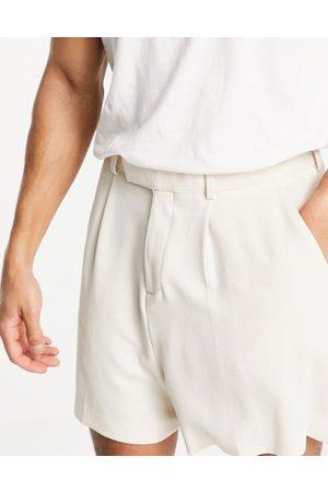 ASOS DESIGN Soft tailored pleated wide leg bermuda suit shorts in ecru crepe