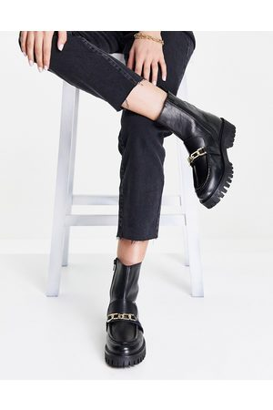 ASRA Bobbie chunky flat boots with gold chain in black leather