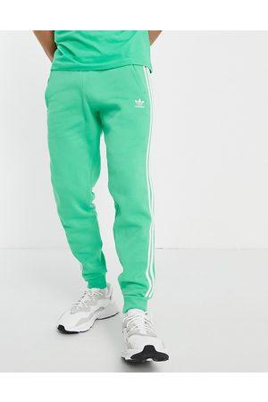 adidas Adicolor three stripe joggers in green