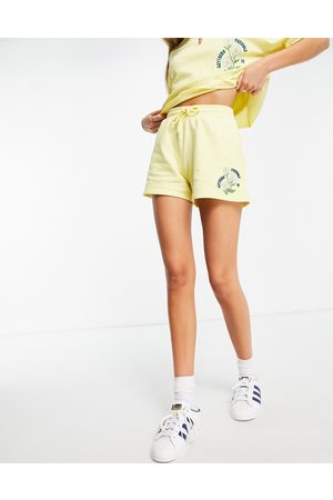 Reclaimed Vintage Inspired jersey shorts with daisy embroidery in yellow co ord