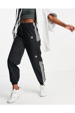adidas Adicolor disturbed three stripe track pants in black with pockets