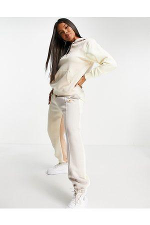 Nike Metallic Swoosh colour block joggers in cream and grey neutrals